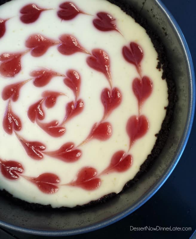 Cheesecake in springform pan with strawberry hearts.