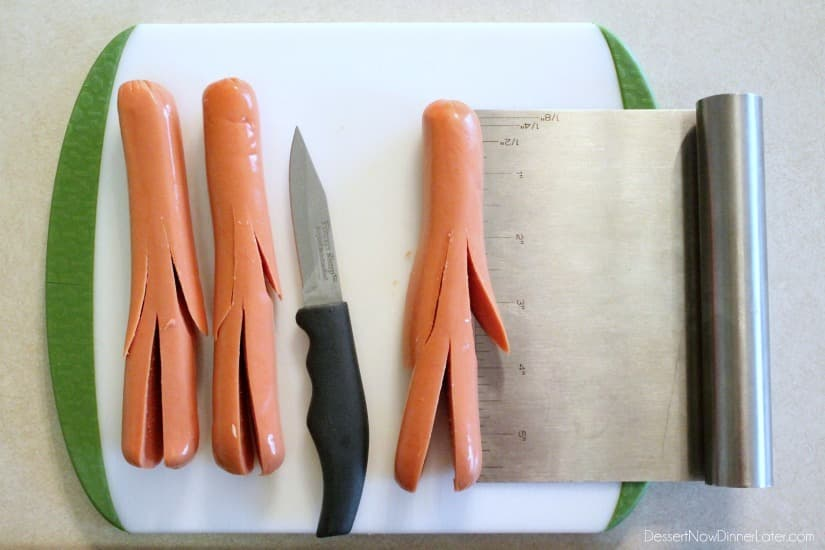 Hot dogs with arms and legs cut with a knife.