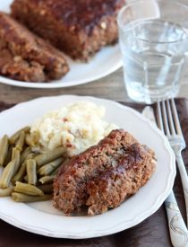 Steak Lovers' Meatloaf - A1 steak sauce, garlic, and onions on the inside, with more steak sauce slathered on the outside, makes this meatloaf both moist and delicious! From DessertNowDinnerLater.com