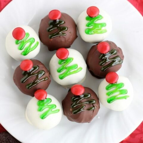 These traditionally made OREO Cookie Balls are decorated with green gel and a red candy coated chocolate piece for a festive Christmas Tree treat! From DessertNowDinnerLater.com