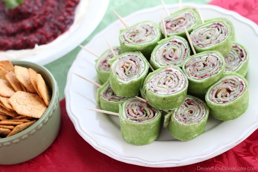 Cranberry Turkey Pinwheels have layers of cream cheese, spicy-sweet cranberry salsa, and thinly sliced turkey all rolled up in a spinach tortilla for a delicious party appetizer! From DessertNowDinnerLater.com