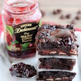 Dark Chocolate Cherry Brownies are made from a doctored box mix that has cherry filled morsels and cherry preserves swirled throughout. From DessertNowDinnerLater.com