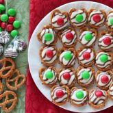 These festive Christmas Pretzel Hugs are melted just enough to press an M&M on the top. Let the chocolate set back up and then package them for neighbor gifts, or place them on a plate for the perfect salty-sweet treat! From DessertNowDinnerLater.com