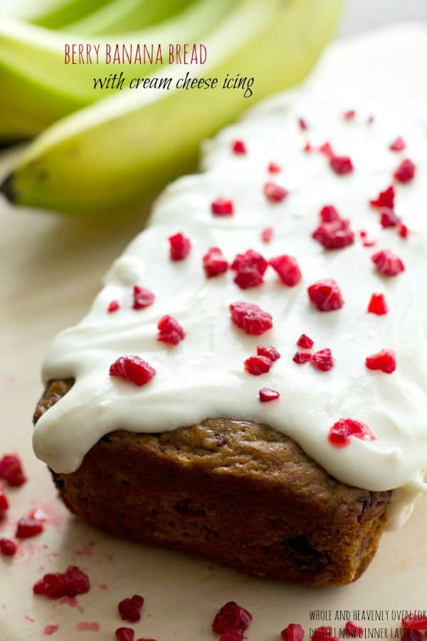 This super-soft and moist banana bread is exploding with a double-delight of juicy berries and perfectly covered in a tangy cream cheese icing. | dessertnowdinnerlater.com