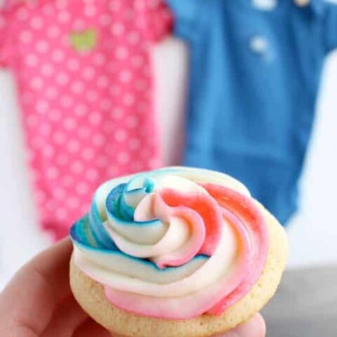 These Gender Reveal Cupcakes have pink, blue, and white swirled frosting on top that hides the secret colored heart in the center of the cupcake revealing the baby's gender when you bite into it! (Step-by-Step Photo Tutorial)