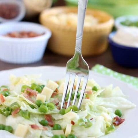 Sarah's Salad from Utah's Lion House restaurant uses crisp iceberg lettuce, peas, bacon, green onions, and swiss cheese tossed in a simple, sweet dressing.
