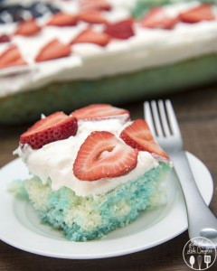 Red strawberries, white cake, and blue jello, come together to create this simple and delicious patriotic Red, White, and Blue Poke Cake perfect for the 4th of July!