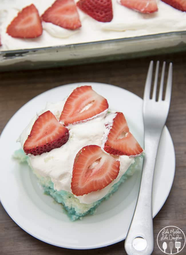 Red strawberries, white cake, and blue jello, come together to create this simple and delicious patriotic Red, White, and Blue Jello Poke Cake perfect for the 4th of July!