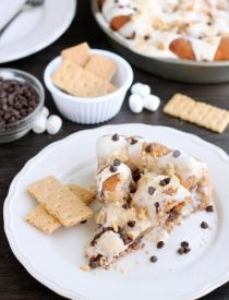 Crushed graham crackers, mini chocolate chips, and mini marshmallows are rolled up in buttery cinnamon sugar rolls to create this S'mores Cinnamon Roll Cake. Top it all off with a marshmallow frosting and extra toppings for a delicious dessert!