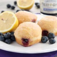 These Jelly Filled Mini Donuts make the perfect breakfast or dessert! Lemon glazed donuts are made easy with refrigerated biscuit dough, and are stuffed with a naturally sweetened blueberry lemon fruit spread.