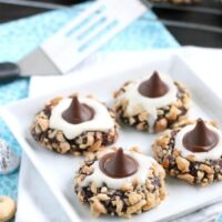 Chocolate cookie dough is rolled in nuts and topped with buttercream and chocolate kisses to create these thick and chewy Chocolate Cream Thumbprint Cookies.