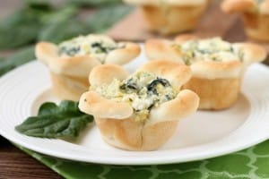 Creamy Spinach Artichoke Dip is baked in the center of bread cups that are shaped to look like blooming flowers. A fun and delicious Easter appetizer.