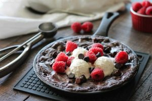 This fudgy skillet brownie is made with a boxed mix for a quick dessert for two! Eat it warm from the oven topped with ice cream, chocolate chips, and fresh raspberries for an extra special treat!