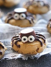 Not all Halloween food has to be gross and gory! These super cute spider cookies are made with peanut butter cups, chocolate, candy eyes, and the BEST peanut butter cookie recipe you'll ever try!