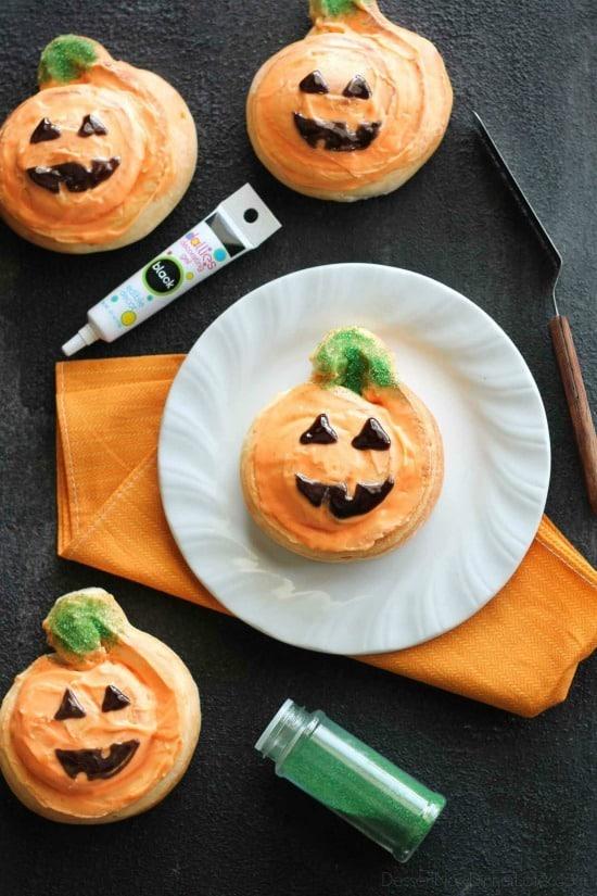 Orange Pumpkin Rolls - Pumpkin shaped orange rolls are decorated to look like jack-o-lanterns for Halloween.