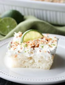 Coconut Lime Poke Cake - a fluffy, white, lime-infused cake that is soaked with coconut cream, and topped with sweetened whipped cream, toasted coconut, and lime zest. It's super moist and full of tropical flavors!