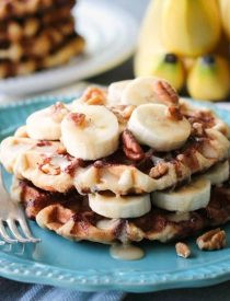 Cinnamon Roll Waffles are topped with freshly sliced bananas, crunchy nuts, and a maple cream cheese drizzle.