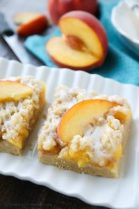 These Peach Crumb Bars are made with fresh summer peaches, sandwiched between a sweet buttery crust and crumb topping, with a hint of cinnamon, and are drizzled with a fresh almond (or vanilla) glaze. The most delicious summer dessert!
