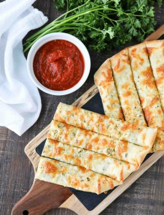 These easy Cheesy Garlic Breadsticks are loaded with garlic, cheese, and herbs for a great tasting breadstick to enjoy for pizza night. Also delicious dipped in marinara sauce!