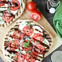 Grilled Caprese Flatbread makes a great summer dinner or appetizer. Freshly grilled bread is topped with mozzarella, tomatoes, basil, and garlic, then drizzled with a simple balsamic glaze.