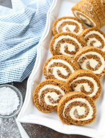This classic Pumpkin Roll is a simple spiced pumpkin cake rolled up with the BEST cream cheese frosting inside. Use parchment paper for easy rolling -- no towel needed.