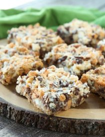 Seven Layer Bars, magic cookie bars, kitchen sink bars, whatever you call them, this classic dessert is easy and delicious. A graham cracker crust, chocolate, white chocolate, and butterscotch chips, nuts, and shredded coconut are melded together with sweetened condensed milk.