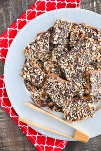 Cracker Toffee (aka Christmas Crack) is so easy to make and highly addictive! Saltine crackers are coated in a quick toffee layer and topped with chocolate and nuts.