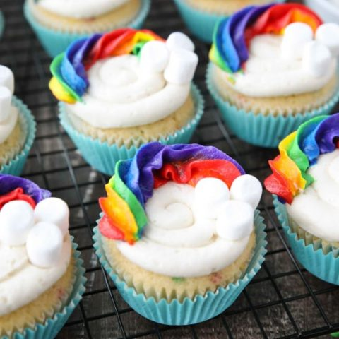 These Funfetti Rainbow Cupcakes are colorful inside and out! Homemade funfetti cupcakes are moist and full of sprinkles. Then topped with a colorful buttercream rainbow and mini marshmallow clouds. Super fun for birthday cupcakes or perfectly festive for St. Patrick's Day!
