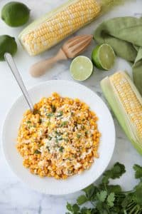 Mexican Street Corn Salad is easy, creamy, and packed with flavor! Your favorite roasted Mexican street corn (Elote) is cut off the cob (to make Esquites) and is served with a spoon, for a delicious summer side dish!
