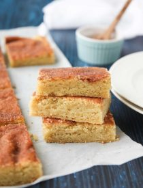 Snickerdoodle Bars transform classic snickerdoodle cookies into easy-to-make blondies. Thick, soft, buttery cookie bars are topped with plenty of cinnamon-sugar. These flavorful, melt-in-your-mouth dessert bars make enough to serve a crowd. Perfect for potlucks, picnics, and parties.