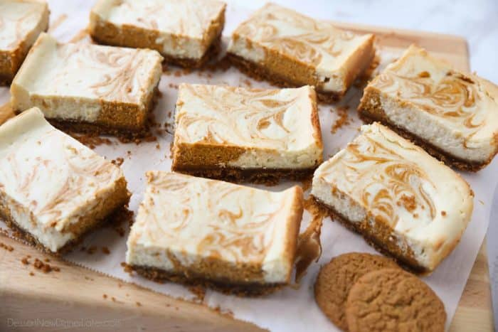 Pumpkin Swirl Cheesecake Bars have a buttery gingersnap crust, with ribbons of creamy vanilla and spiced pumpkin cheesecake marbled on top. A delicious dessert for fall or Thanksgiving.