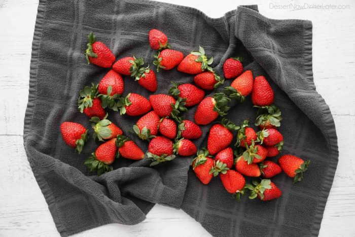 Drying strawberries completely with a towel will ensure the chocolate will stick to the fruit.
