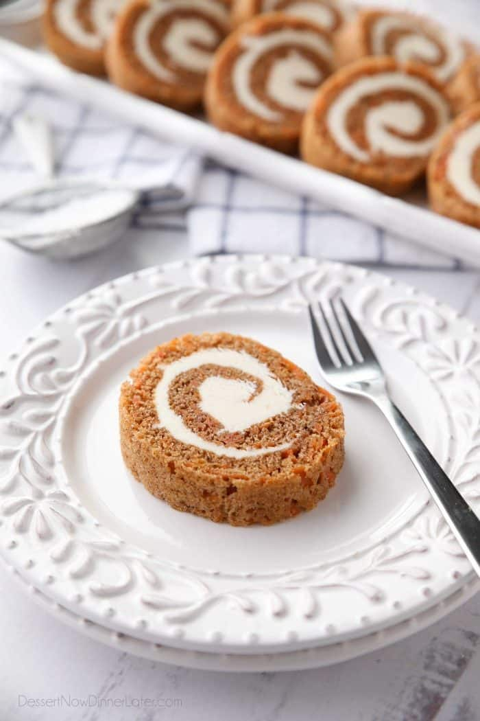 A slice of Carrot Cake Roll with cream cheese frosting inside.