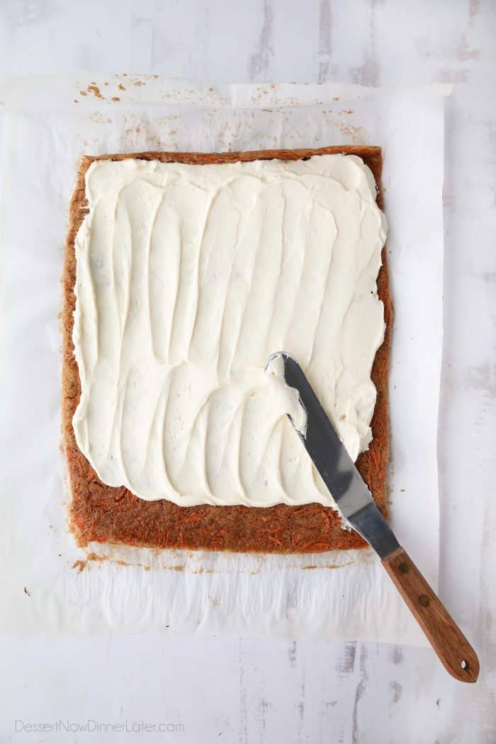 Cream cheese frosting being spread over a thin layer of carrot cake.