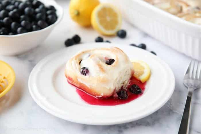 A lemon blueberry sweet roll on a plate with blueberry sauce and a slice of lemon.