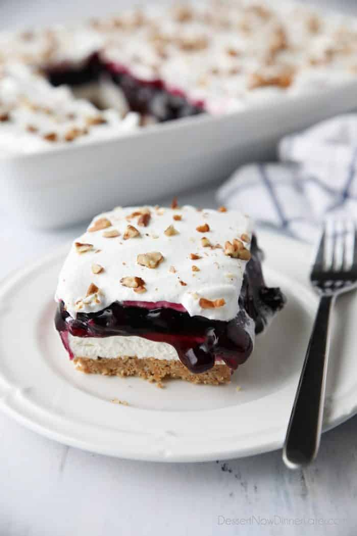 Blueberry Delight (aka Blueberry Lush) is an easy layered dessert with a graham cracker and pecan crust, no bake cheesecake, blueberry pie filling, and cool whip topping. A light, fruity, and delicious summer dessert with minimal baking.