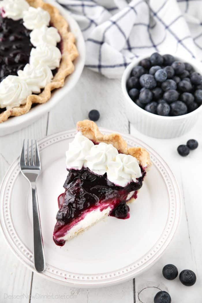 Slice of blueberry cream cheese pie on a plate with whipped cream on top.