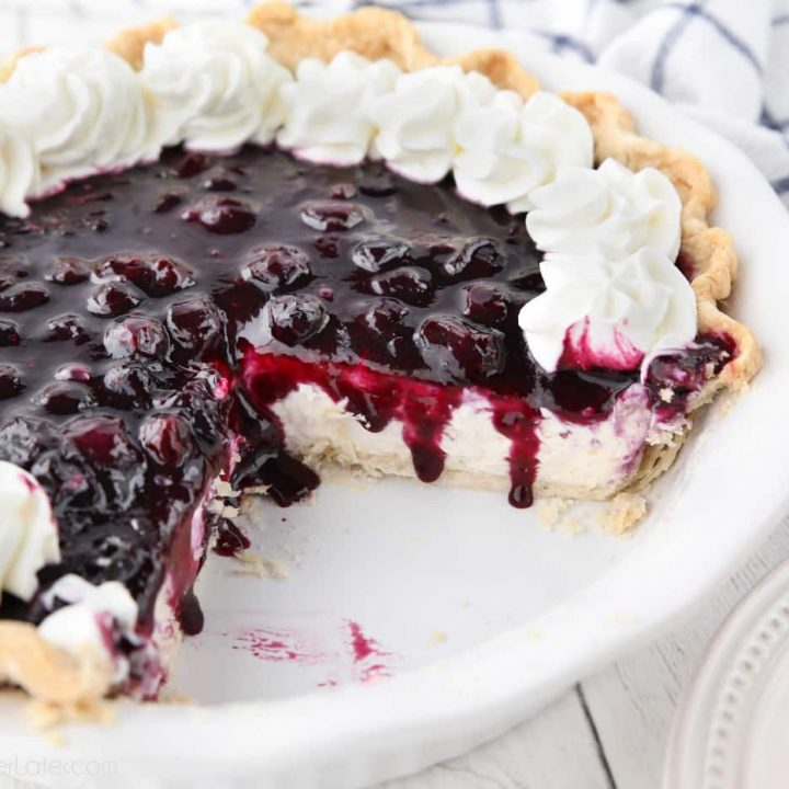 Blueberry Cream Cheese Pie with whipped cream on top and a couple slices missing from dish.