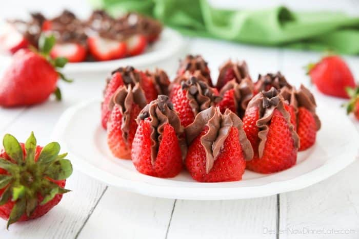 Plate of strawberries filled with no bake chocolate cheesecake filling and topped with mini chocolate chips.