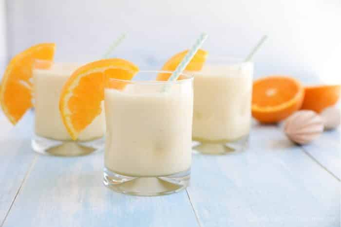 Orange Julius smoothies in cups with straws and fresh orange slices.