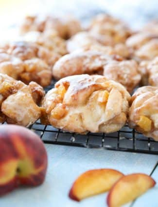 Glazed Peach Fritters Donuts on a cooling rack.