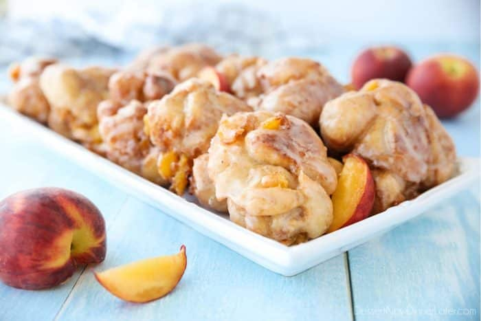 Glazed Peach Fritters Donuts on a platter with fresh peaches.