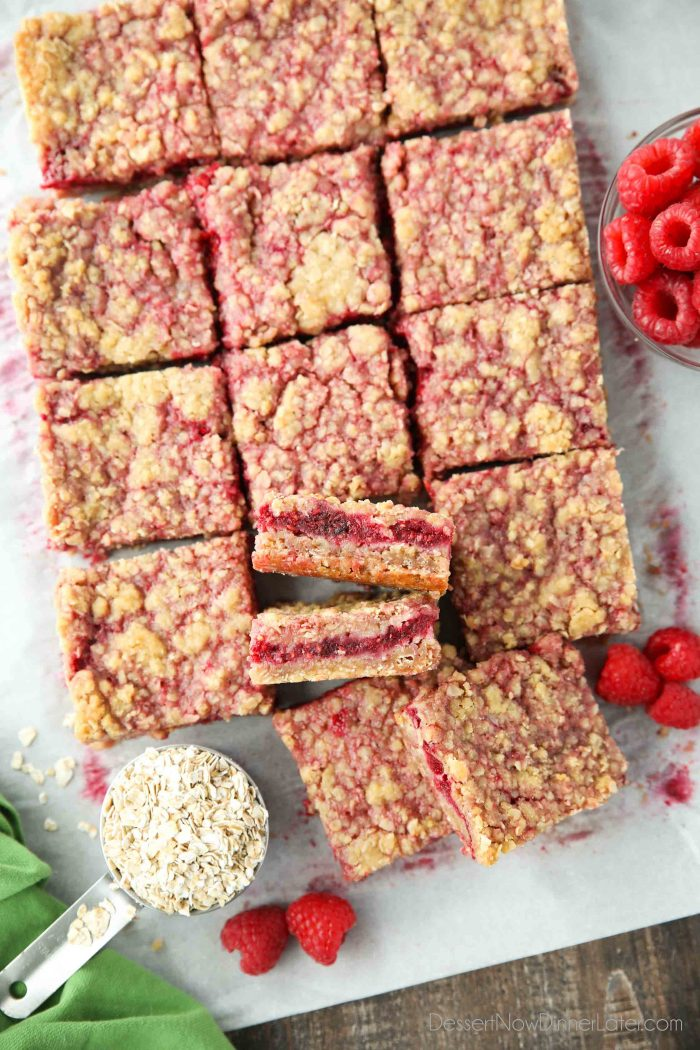 Raspberry Crumble Bars on parchment paper with fresh raspberries and oats.