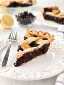 Slice of homemade blueberry pie made with frozen blueberries and simple ingredients to create a thick (not runny) pie filling from scratch.