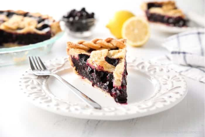 Slice of easy homemade blueberry pie on a plate with a fork.