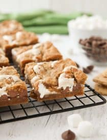 Gooey s'mores bars on a cooling rack with marshmallow fluff and chocolate chips in the center. | Dessert Now Dinner Later
