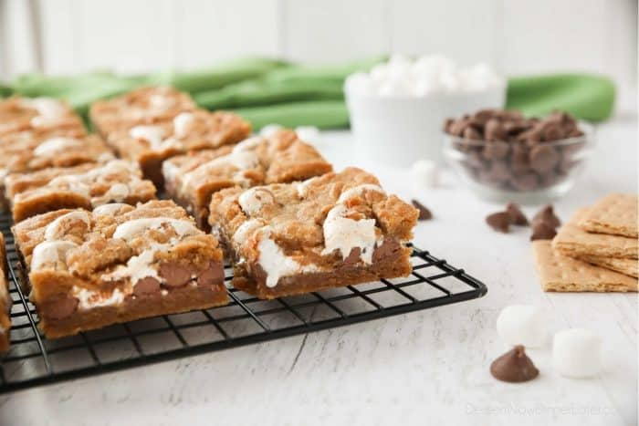 Gooey s'mores bars on a cooling rack with ingredients of graham crackers, chocolate chips, and mini marshmallows nearby. | Dessert Now Dinner Later
