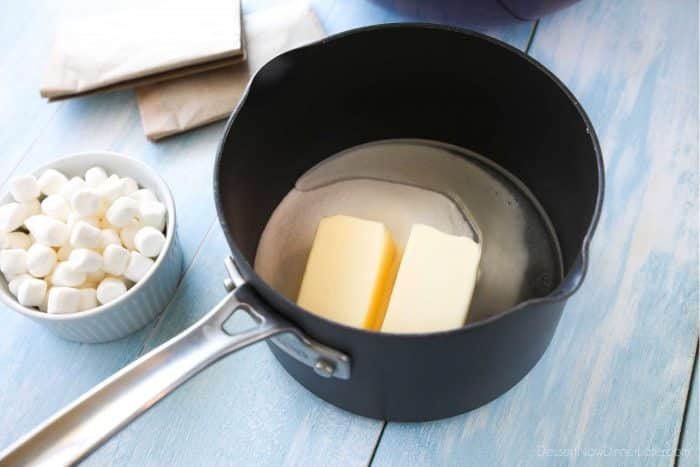 Marshmallow Popcorn starts by melting butter, sugar, and corn syrup together.