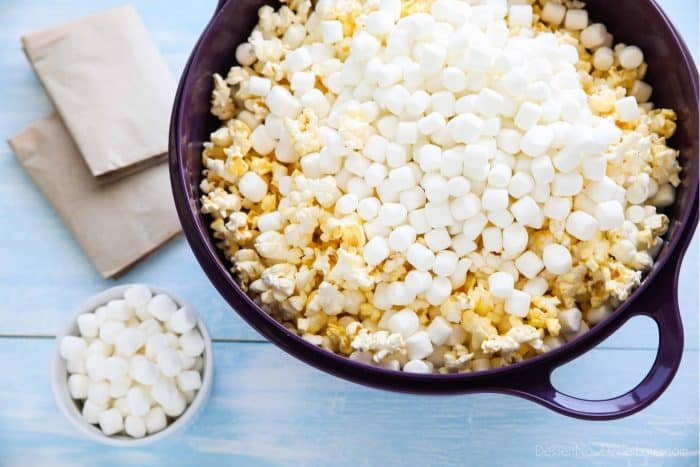 Popcorn and mini marshmallows are placed in a big bowl before mixing.
