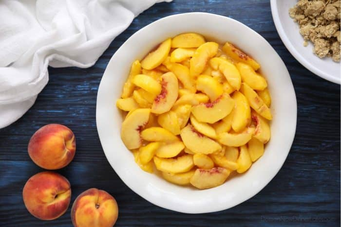 Prepared peaches for Peach Crisp in a 9-inch pie dish. May alternately use an 8 or 9-inch square baking dish.